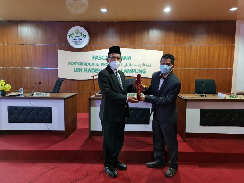 Penyerahan Piagam oleh Ketua Sidang kepada Dr. Rada, M.Pd.I